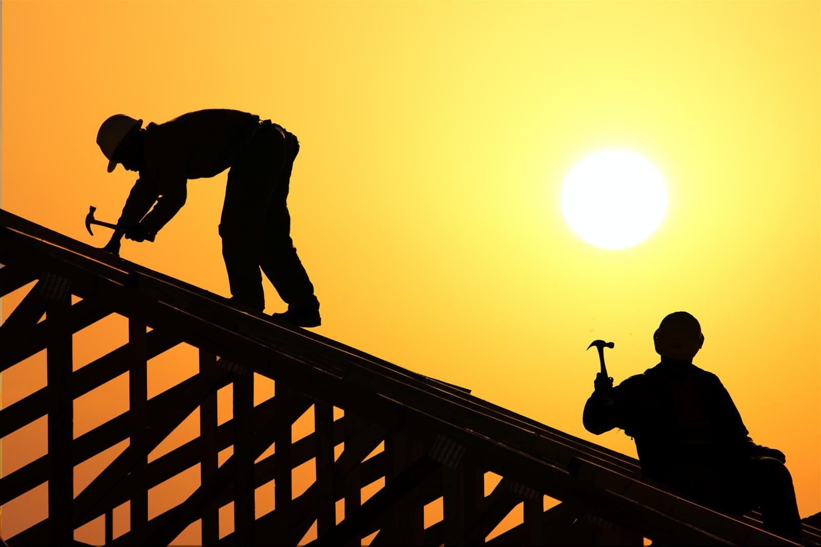 image of two roofers on top of roof with sun setting